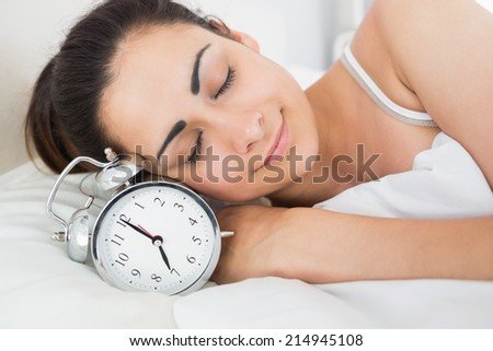 Beautiful young woman sleeping in bed with alarm clock at home