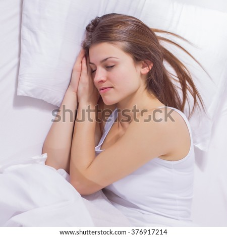 Beautiful young woman sleeping in the bed. Relaxing and peaceful  - stock photo