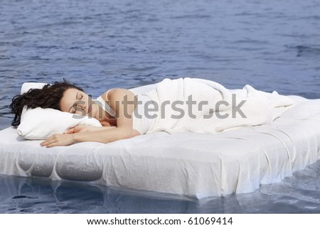 Beautiful young woman sleeping on the white bed in the sea - stock photo