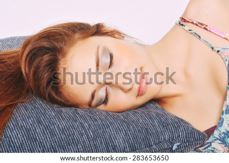 Beautiful young woman sleeping with her head over a pillow - stock photo