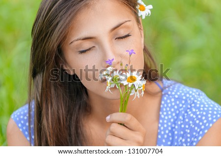 Beautiful young woman smelling bouquet of daisies, against summer green park.