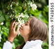 Beautiful young woman smelling white jasmin flowers - stock photo