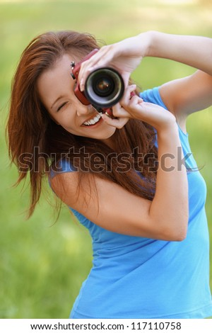 Beautiful young woman smiles and photographs, against background of summer green park. - stock photo