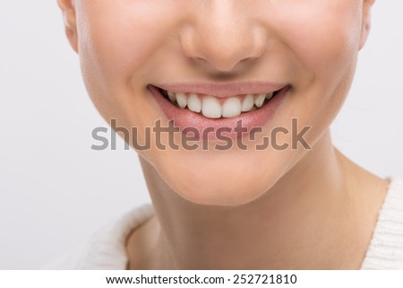 Beautiful young woman smiling an showing perfect white healthy teeth - stock photo