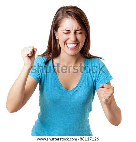 beautiful young woman smiling and clenching fists in a show of excitement and triumph