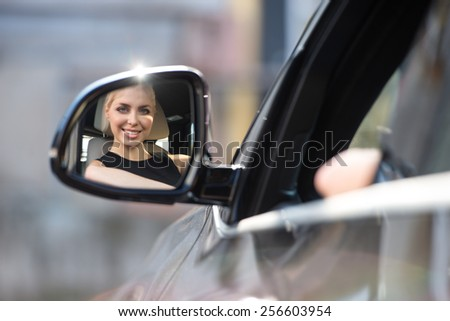 Beautiful young woman smiling and looking at side view mirror in the car - stock photo