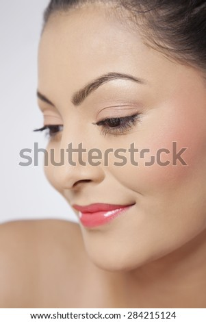 Beautiful young woman smiling and looking down - stock photo