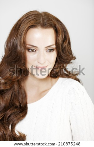 Beautiful young woman smiling and looking relaxed in a white jumper