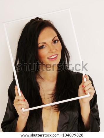 Beautiful young woman smiling and looking through picture frame - stock photo