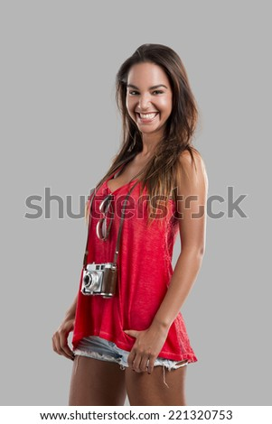 Beautiful young woman smiling and posing with a old vintage camera