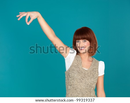 beautiful, young woman, smiling and pretending to hold something with her fingers, on blue background