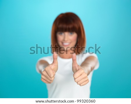 beautiful, young woman smiling and showing an ok sign with her hands, on blue background - stock photo