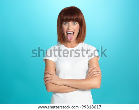 beautiful, young woman smiling and showing her tongue, on blue background