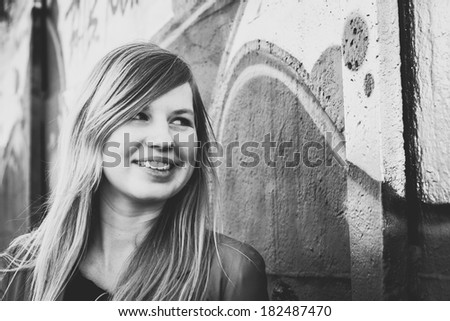 Beautiful young woman smiling at the graffiti wall - stock photo