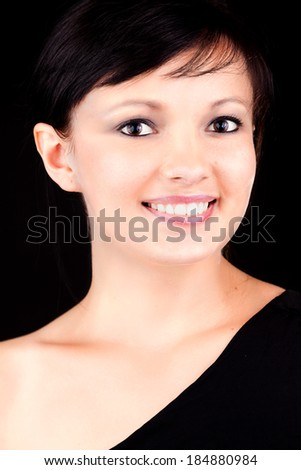 beautiful young woman, smiling, black background - stock photo