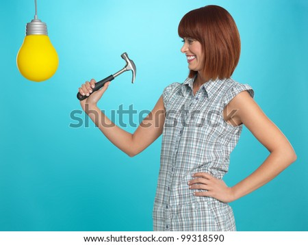 beautiful, young woman smiling, smashing a lightbulb with a hammer, on blue background
