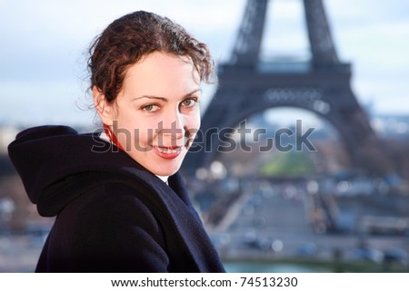 beautiful young woman smiling, view of Eiffel Tower at winter