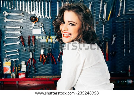 Beautiful young woman smiling with vintage car shop bench background - stock photo