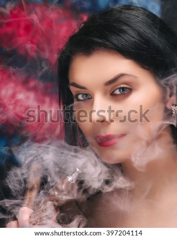 Beautiful young woman smoke hookah. Close-up studio portrait.
