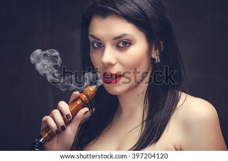 Beautiful young woman smoke hookah. Close-up studio portrait. - stock photo