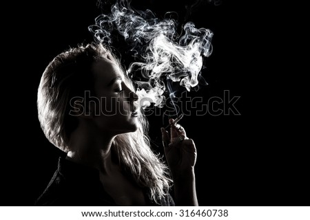 Beautiful young woman smoking a cigarette over black background - stock photo