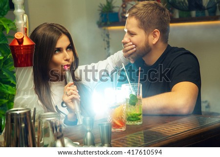 beautiful young woman smoking a hookah and closes the mouth hand to the guy behind the bar - stock photo