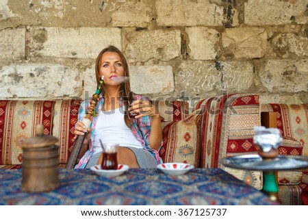 Beautiful young woman smoking a hookah and drinking tea in a cafe, Istanbul, Turkey