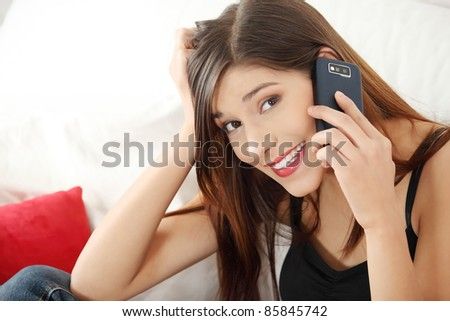 Beautiful young woman speaking by mobile phone - indoors