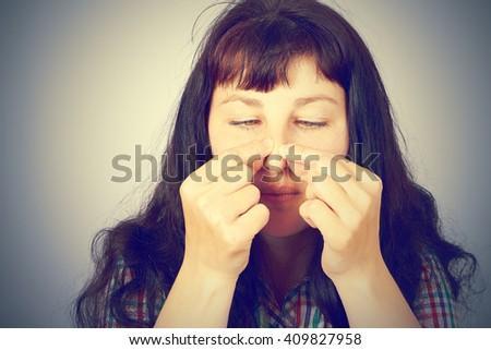 beautiful young woman squeezing pimples on her nose - stock photo