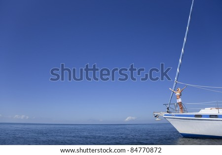 Beautiful young woman standing arms raised on the bow of a sail boat on a tranquil calm blue sea