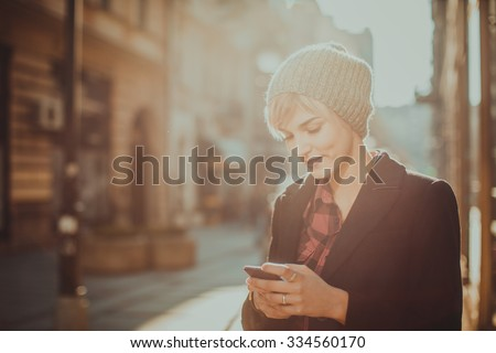 Beautiful young woman standing at the street and using her mobile phone - stock photo