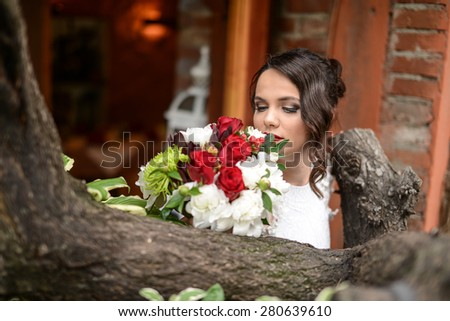beautiful young woman standing by a tree posing with a bouquet of flowers