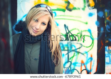 Beautiful young woman standing by the road in front of graffiti wall - stock photo