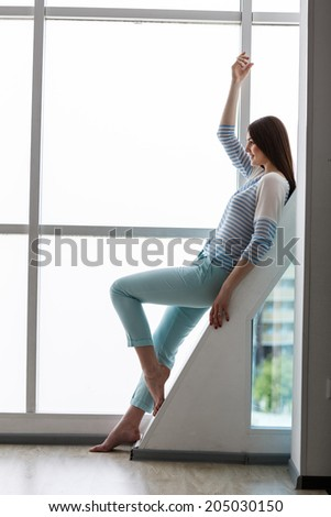Beautiful young woman standing in front of window at room. Space for copy. - stock photo