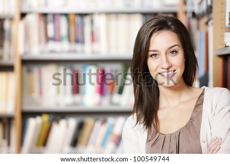 Beautiful young woman standing in library - stock photo