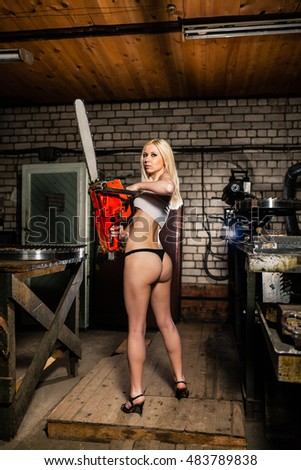 Beautiful young woman standing in the garage with chainsaw