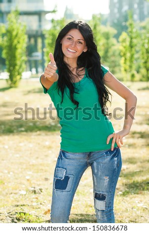 Beautiful young woman standing in the park and showing thumb up,Woman showing ok sign