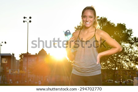 Beautiful young woman standing in workout attire and holding a water bottle. Setting sun directly behind her creates a warm and soft light on scene. - stock photo