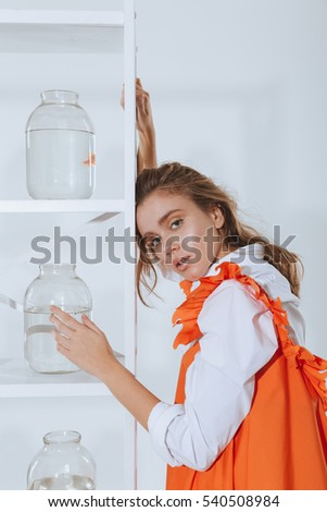 Beautiful young woman standing near shelves with golden fishes in jars over white background