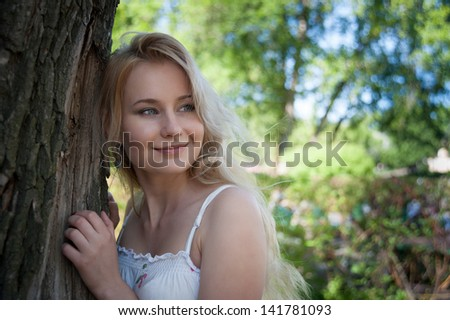 beautiful, young woman standing near the tree in the park
