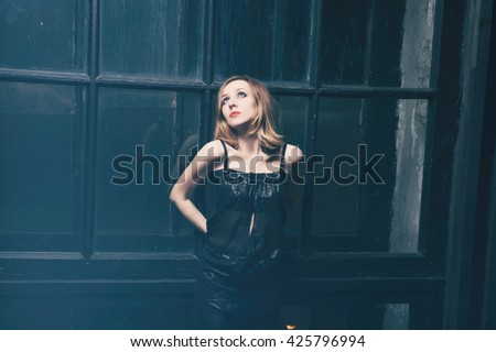 Beautiful young woman standing near the window at night - stock photo