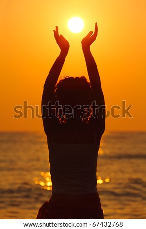 beautiful young woman standing on beach, watching sunset, holding  sun in hands - stock photo