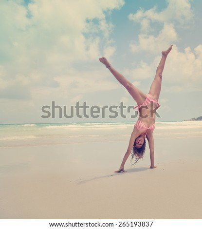 Beautiful young woman standing on hands on the beach, image with retro toning