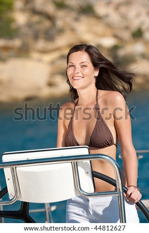 Beautiful young woman standing on luxury boat holding rudder - stock photo