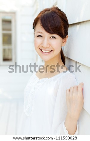 Beautiful young woman standing on terrace. Portrait of asian. - stock photo