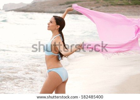 Beautiful young woman standing on the shore of a natural sand beach surrounded with mountains, holding up a pink fabric sarong floating in the breeze enjoying her holiday. Travel lifestyle. - stock photo