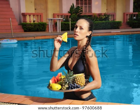 Beautiful young woman standing on the side of the pool with fruit - stock photo