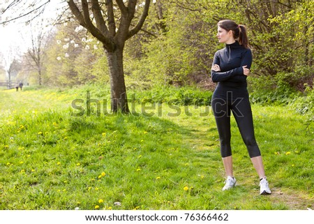 Beautiful young woman standing outdoors in sports clothing - stock photo