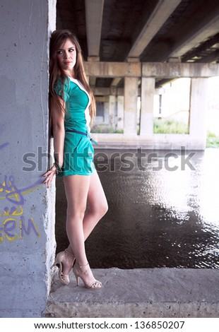 Beautiful young woman standing under the bridge