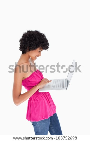 Beautiful young woman standing upright while holding a laptop - stock photo